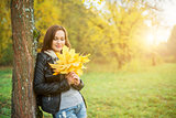 Young woman holding yellow leaf
