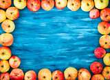 Frame of fresh red apples on  painted blue wooden background