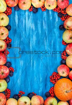 Autumn frame of apples, pumpkin, rowan on  painted blue wooden b