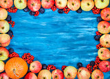 Autumn frame of apples, pumpkin, rowan on  painted blue wooden b