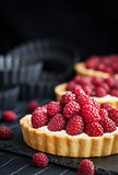 Delicious raspberry mini tarts on dark background
