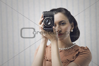 Beautiful young woman with a old camera