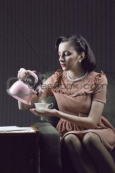 Beautiful woman sitting at armchair, drinking tea