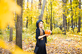Halloween Witch with Pumpkin in a forest.