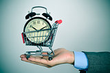 businessman with an alarm clock in a shopping cart