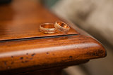 Wedding rings on the edge of a wooden table