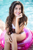 Girl in swimsuit sits on rubber ring