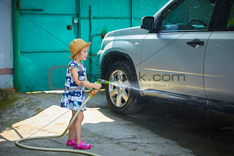 Little girl helps her parents to wash the car