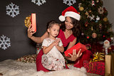 Mother with daughters open a Christmas gift