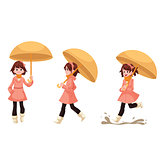 Little girl in a raincoat with umbrella enjoying rainy weather