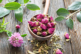 Dry rose tea buds in wooden spoon