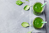 Spinach smoothie Healthy drink in glass jar on grey stone background. Copy space Top view