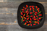 Red and green hot peppers on a black plate in style  rustic