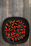 Red and green hot peppers on a black plate  old wooden boards
