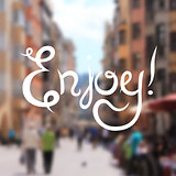 Enjoy hand lettering design inscription on blur background, vector illustration