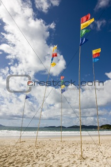 Flagpoles with colorful flags on the beach