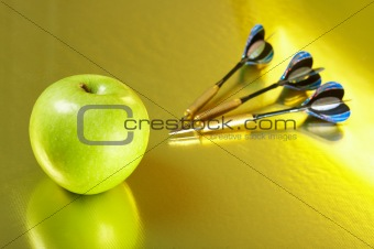 Apple and the darts laying on a golden background