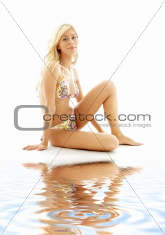 blond in bikini sitting on white sand