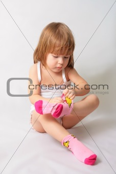 Small girl is puting on the socks