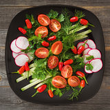 Greens and vegetable salad on a black plate in style  rustic