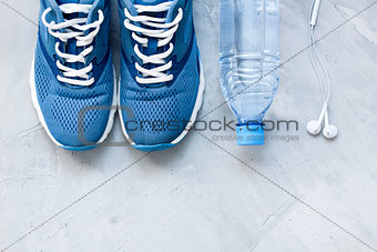 Flat lay sport shoes, bottle of water and earphones on gray conc