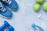 Flat lay sport shoes, dumbbells, earphones, apples, bottle of wa