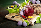 Plums and jar of jam on table