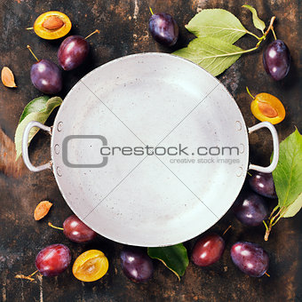 Old bowl and plums on a rural background