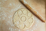 dough rolled with circles, rolling pin