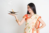 Girl with Indian sari dress holding oil lamp