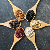 various legumes in wooden spoons