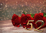 birthday concept with red roses on wooden desk. fifty-second. 52nd. 3D render