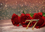 birthday concept with red roses on wooden desk. seventy-seventh. 77th. 3D render