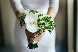 Bride with a bouquet of white Orchid in the hands