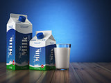 Milk carton packand glass on blue background.