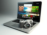 Photo camera and laptop with image viewer on the screen. Digital