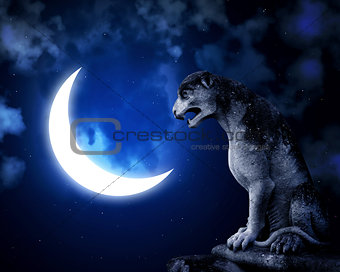 Ancient lion statue and crescent on night sky background