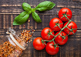 Fresh tomatoes with basil and spices jar on grunge board