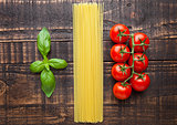 Fresh tomatoes with raw spagetti and basil on gunge background