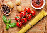 Fresh tomatoes with vegetables  and spagetti on wooden board