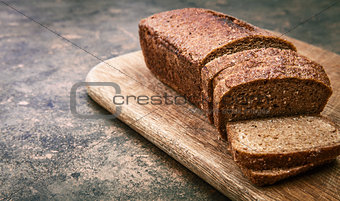 Fresh bread cut on wooden board