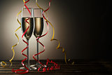 Two champagne glasses with decorative yellow and red ribbons