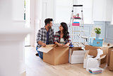 Hispanic Couple Moving Into New Home And Unpacking Boxes