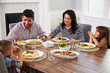 Hispanic Family Enjoying Meal At Table