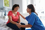 Nurse Making Home Visit To Senior Hispanic Woman