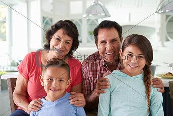 Hispanic Grandparents At Home With Grandchildren