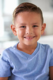 Head And Shoulders Portrait Of Smiling Hispanic Boy At Home