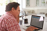 Confused Senior Hispanic Man Sitting At Home Using Laptop