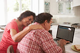 Confused Senior Hispanic Couple Sitting At Home Using Laptop