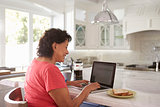 Senior Hispanic Woman Sitting At Home Using Laptop